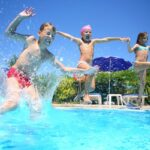 Two little girls and boy fun jumping into the swimming pool, sho