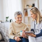 A health visitor with tablet explaining a senior woman how to take pills.
