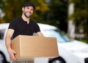 32276643 - smiling delivery man holding a paper box