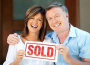 Happy mature couple holding sold sign